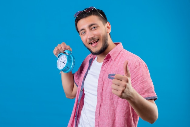 Young handsome traveler guy holding alarm clock looking positive and happy smiling showing thumbs up standing over blue background