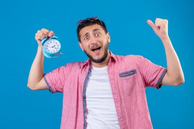 青い背景に上げられた手で驚いて、驚いて立っている目覚まし時計を保持している若いハンサムな旅行者男