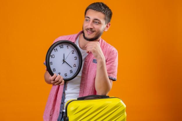 オレンジ色の背景に肯定的な立っているウィットスーツケースを考えてあごに手でよそ見時計を保持している若いハンサムな旅行者男