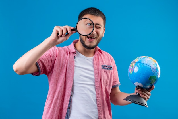 젊은 잘 생긴 여행자 사람이 지구를 들고 돋보기를 통해 카메라를보고 유쾌하게 파란색 배경 위에 서서 웃고