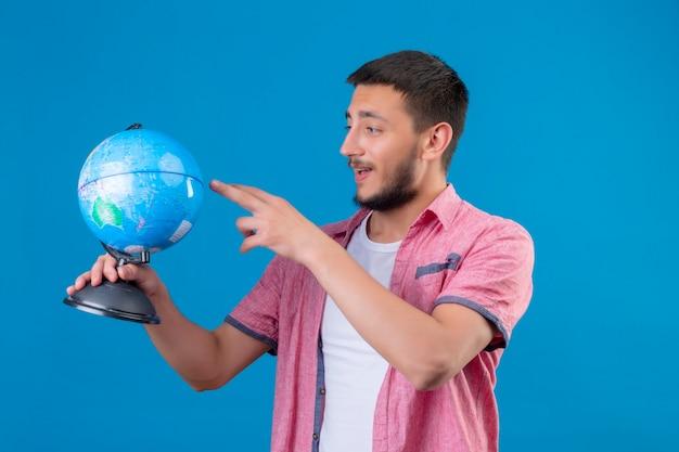 Молодой красивый путешественник парень держит глобус, глядя на него, улыбаясь со счастливым лицом, стоящим на синем фоне