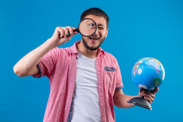 Giovane globo bello della tenuta del tipo del viaggiatore ed esaminare macchina fotografica tramite la lente d'ingrandimento che sorride allegramente controllando fondo blu