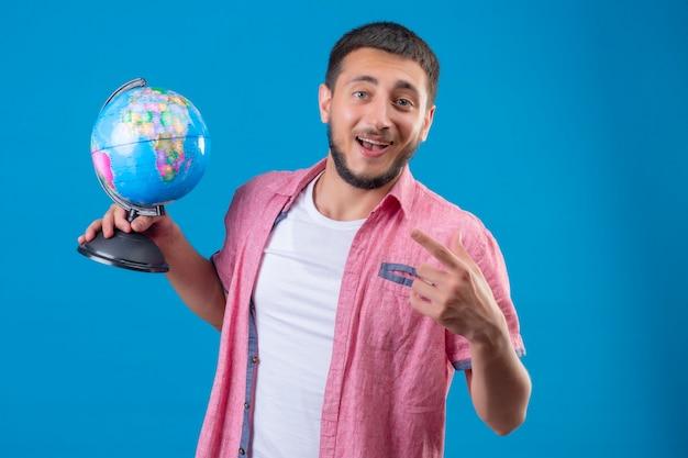 Молодой красивый путешественник парень держит глобус, улыбаясь счастливым лицом, указывая пальцем в сторону, стоя на синем фоне