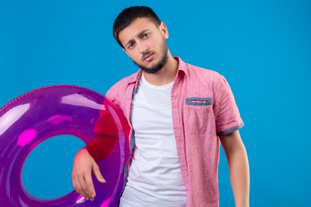 Young handsome traveler guy holding inflatable ring looking at camera with sad expression standing over blue background