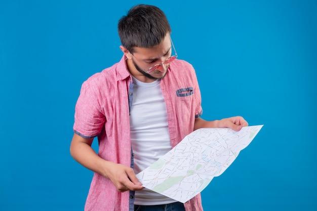 青い背景の上に立って興味を持ってそれを見て地図を保持している若いハンサムな旅行者男