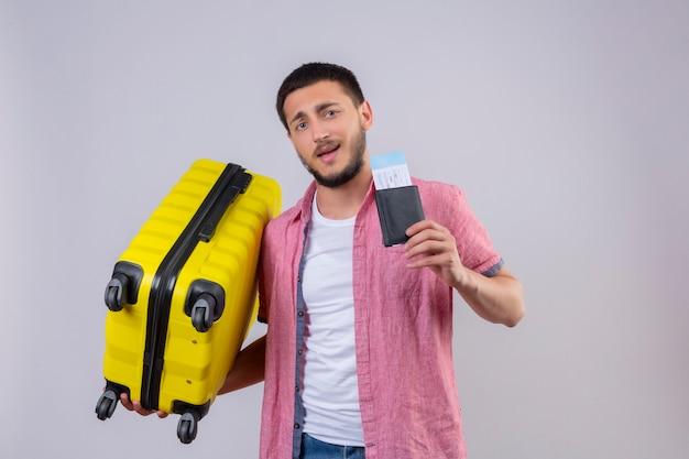 白い背景の上に幸せと肯定的な立っている顔に自信を持って笑顔でカメラ目線のスーツケースと航空券を保持している若いハンサムな旅行者男