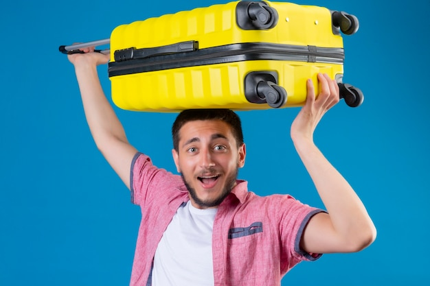 Young handsome traveler guy holding suitcase on his head looking joyful with happy smile on face standing over blue background