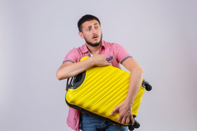 Young handsome traveler guy holding suitcase looking aside confused with sad expression on face standing over white background