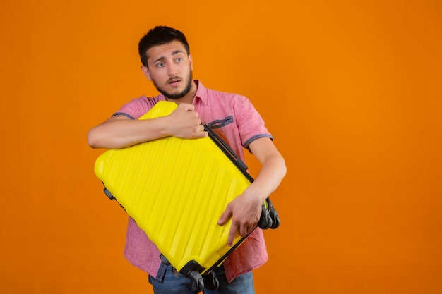 Young handsome traveler guy holding suitcase looking aside with sad expression on face unhappy standing over orange background