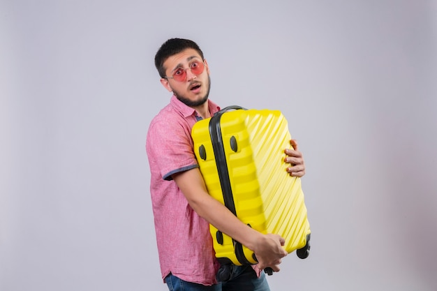 Young handsome traveler guy holding suitcase looking at camera confused  with sad expression on face standing over white background
