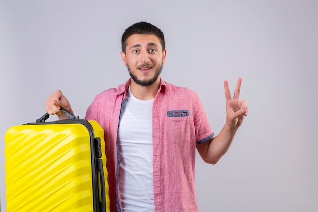 Young handsome traveler guy holding suitcase looking at camera smiling happy and positive showing number two or victory sign standing over white background