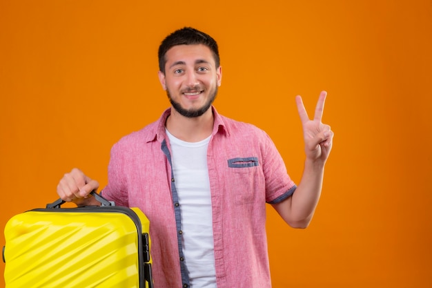 Young handsome traveler guy holding suitcase looking at camera with happy face smiling showing number two or victory sign standing over orange background