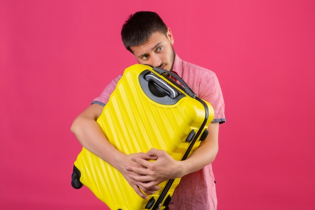 Young handsome traveler guy holding suitcase looking confused with sad expression on face standing over pink background