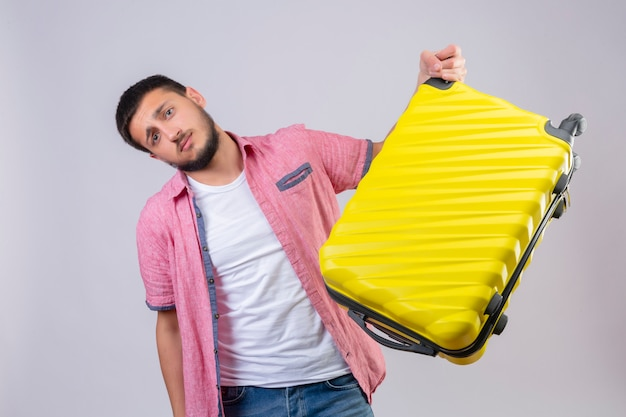 Young handsome traveler guy holding suitcase looking confused with sad expression on face standing over white background