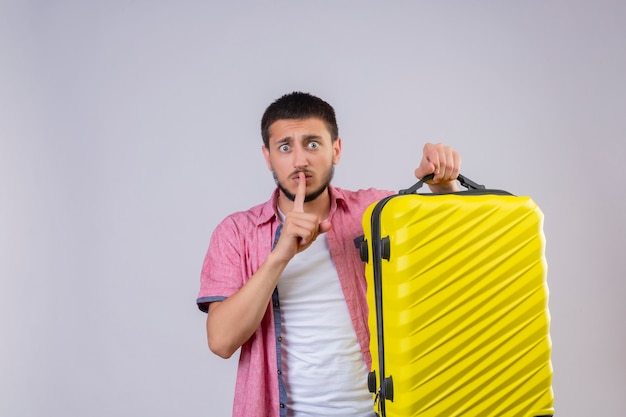 Young handsome traveler guy holding suitcase making silence gesture with finger on lips looking at camera surprised standing over white background