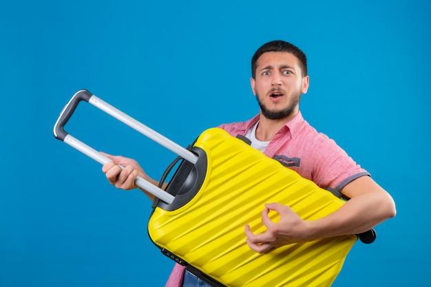 青い背景の上に立って幸せそうな顔でうれしそうな探しているギターとしてスーツケースを保持している若いハンサムな旅行者男