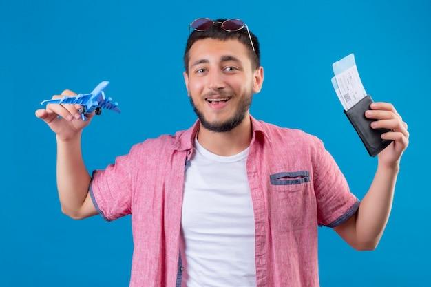 Молодой красивый путешественник, держащий игрушечный самолетик и авиабилеты, глядя в камеру, весело улыбаясь, со счастливым лицом, стоящим на синем фоне