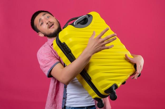 Молодой красивый путешественник, держащий желтый чемодан, выглядит смущенным, стоя на розовом фоне