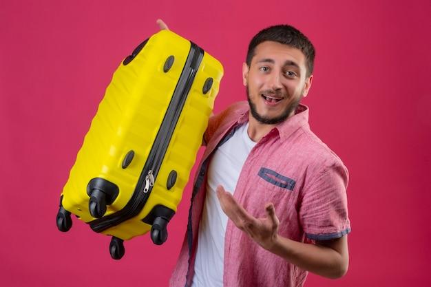 Молодой красивый путешественник, держащий желтый чемодан, весело улыбаясь, указывая рукой, стоящей на розовом фоне
