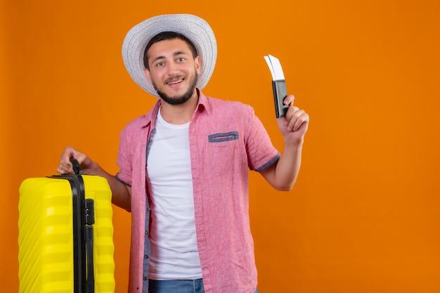 スーツケースと航空券を保持している夏の帽子の若いハンサムな旅行者の男はオレンジ色の背景の上に立って旅行する準備ができて元気に笑って自信を持って自己満足を探して