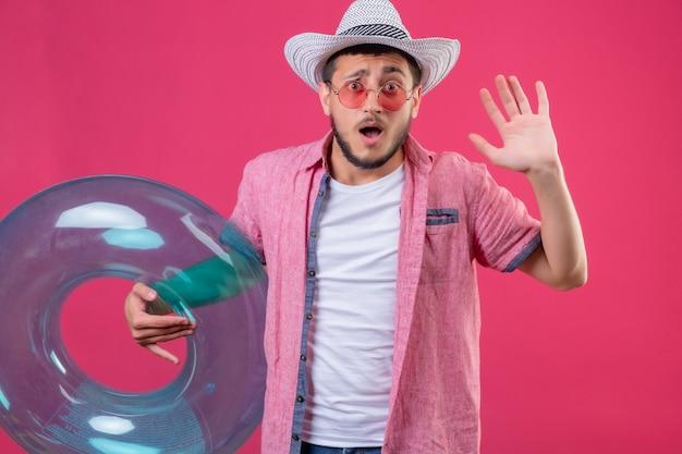 ピンクの背景の上に立っている恐怖の表現で降伏でインフレータブルリングを上げる手を握ってサングラスを身に着けている夏帽子の若いハンサムな旅行者男