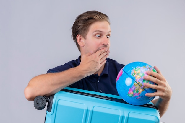 Young handsome traveler guy standing with suitcase holding globe looking at it amazed and surprised covering mouth with hand over white background