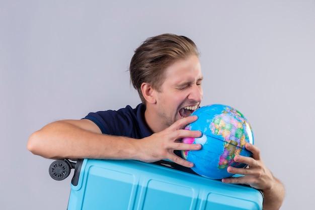 Молодой красивый путешественник, стоящий с чемоданом, держит земной шар безумным и сумасшедшим, пытаясь укусить земной шар на белом фоне