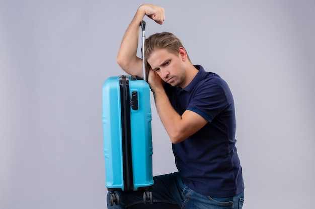 Young handsome traveler guy standing with suitcase with sad expression on face over white background