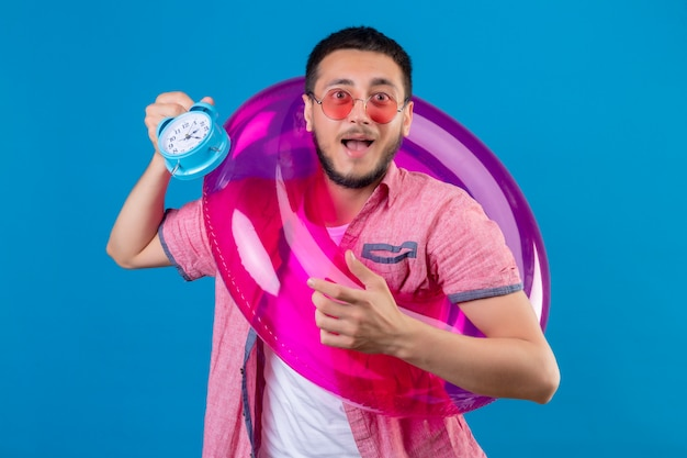 Young handsome traveler guy wearing sunglasses holding inflatable ring and alarm clock looking surprised and happy smiling cheerfully standing over blue background