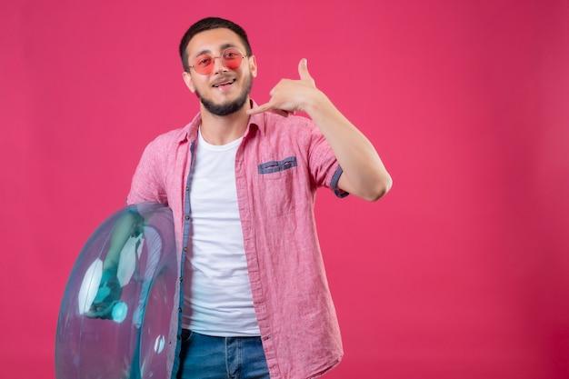Молодой красивый путешественник в темных очках держит надувное кольцо и смотрит в камеру, весело улыбаясь, делая жест на розовом фоне.