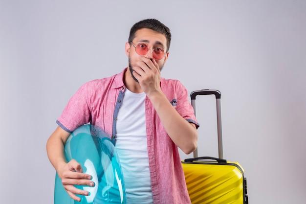 Молодой красивый путешественник парень в солнцезащитных очках держит надувное кольцо, глядя в камеру, удивлен и изумлен, прикрывая рот рукой, стоящей с дорожным чемоданом на белом фоне