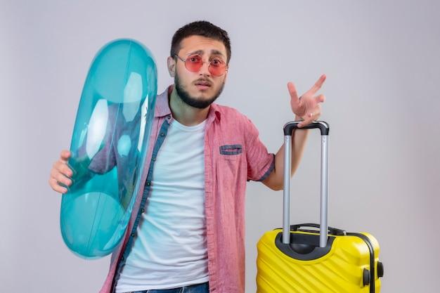Молодой красивый путешественник парень в солнцезащитных очках держит надувное кольцо, глядя в камеру с смущенным выражением лица, стоя с чемоданом путешествия на белом фоне