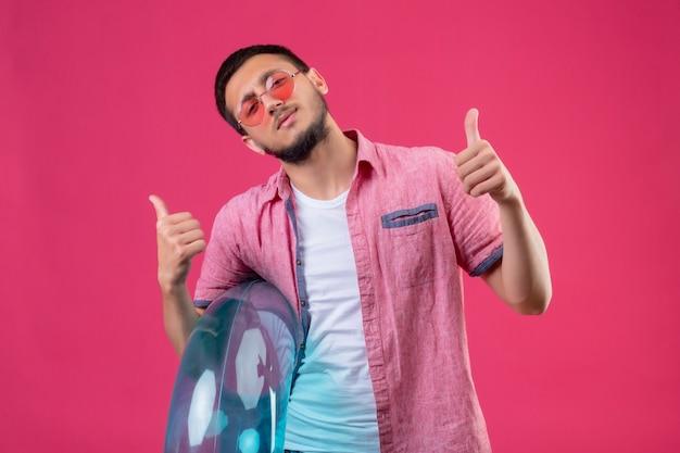 Молодой красивый путешественник в солнцезащитных очках, держащий надувное кольцо, выглядит радостным и счастливым, весело улыбаясь, показывая пальцы вверх, стоя на розовом фоне