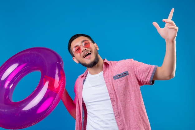 Young handsome traveler guy wearing sunglasses holding inflatable ring looking joyful and happy smiling cheerfully standing over blue backgound