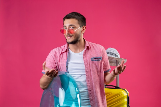 Молодой красивый путешественник в солнцезащитных очках держит надувное кольцо с чемоданом и смотрит в камеру, лукаво улыбаясь с поднятыми руками на розовом фоне