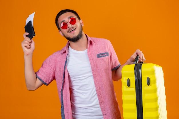 Молодой красивый путешественник в темных очках держит чемодан и авиабилеты, выглядит уверенно, самодовольно улыбаясь, весело готовый к путешествию, стоя на оранжевом фоне