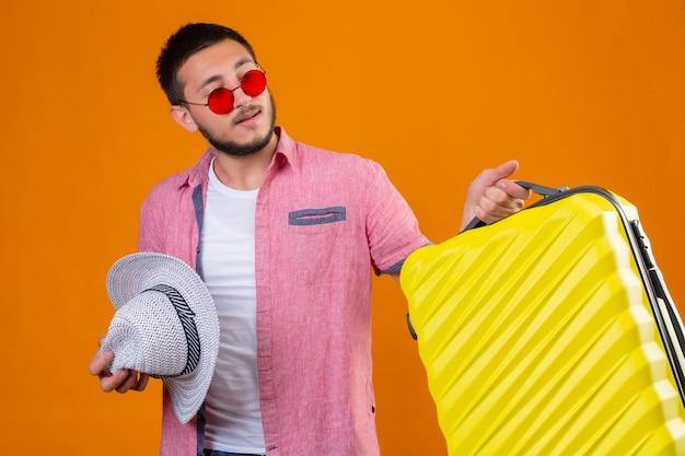 Молодой красивый путешественник в темных очках держит чемодан и летнюю шляпу, выглядит уверенно, самодовольно готовый к путешествию, стоя на оранжевом фоне