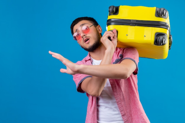青い背景の上に立っている恐怖表現で停止ジェスチャーを作るスーツケース交差手を繋いでいるサングラスを着ている若いハンサムな旅行者男