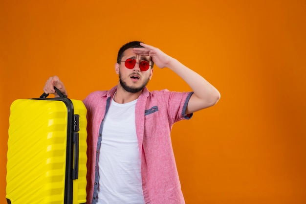 オレンジ色の背景の上に立っている困惑した表情で何かを見るために手で遠くを見てスーツケースを持ってサングラスを着ている若いハンサムな旅行者男