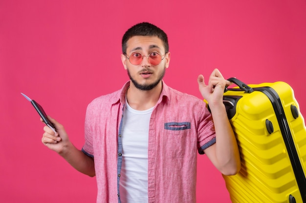 Young handsome traveler guy wearing sunglasses holding suitcase and tickets looking at camera with confuse expression standing over pink background