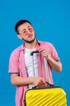 Молодой красивый путешественник в солнцезащитных очках с дорожным чемоданом смотрит в сторону с уверенным и серьезным выражением лица, стоящего на синем фоне