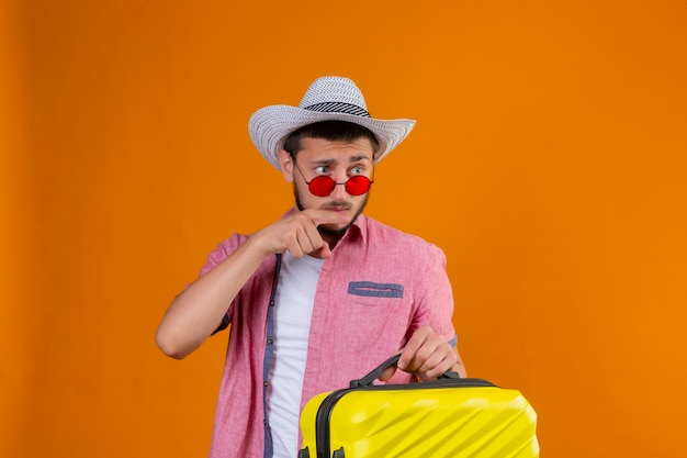 Young handsome traveler guy wearing sunglasses in summer hat holding suitcase looking aside pointing with finger to something with suspicious expression standing over orange background