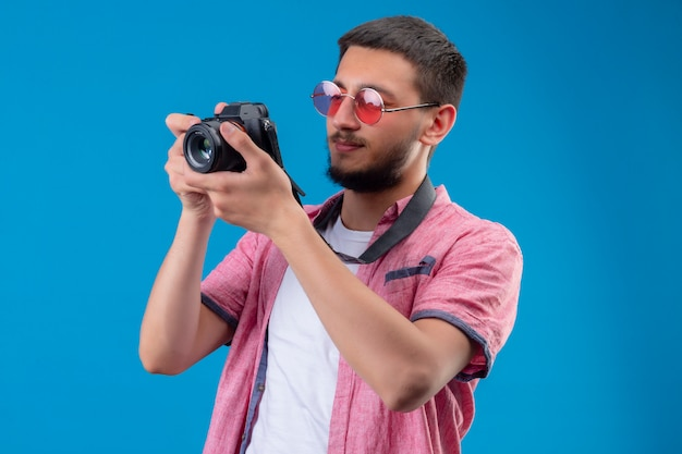 Young handsome traveler guy wearing sunglasses taking a picture with camera standing over blue background