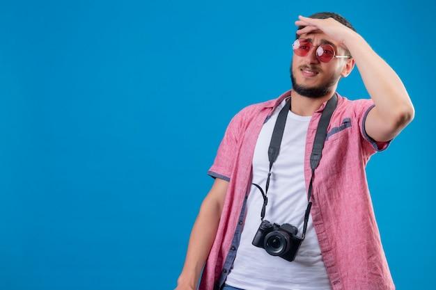 青い背景の上に立っている困惑した表情で何かを見るために手で遠くを見てサングラスを着てカメラを持つ若いハンサムな旅行者男