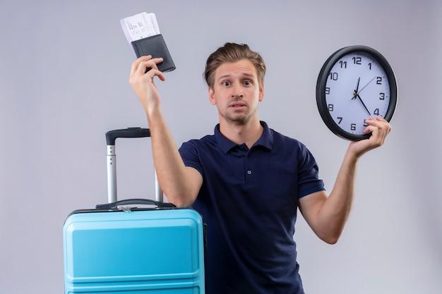 Молодой красивый путешественник мужчина держит авиабилеты и часы, стоя с чемоданом, выглядит удивленным и смущенным на белом фоне