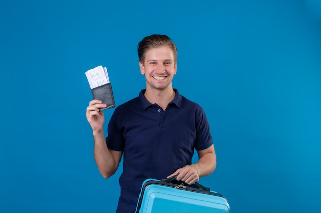 Young handsome traveler man holding air tickets happy and positive looking at camera with big smile on face standing over blue background