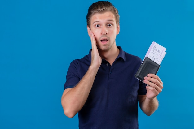 Young handsome traveler man holding air tickets looking surprised and amazed with wide open eyes and mouth standing over blue background