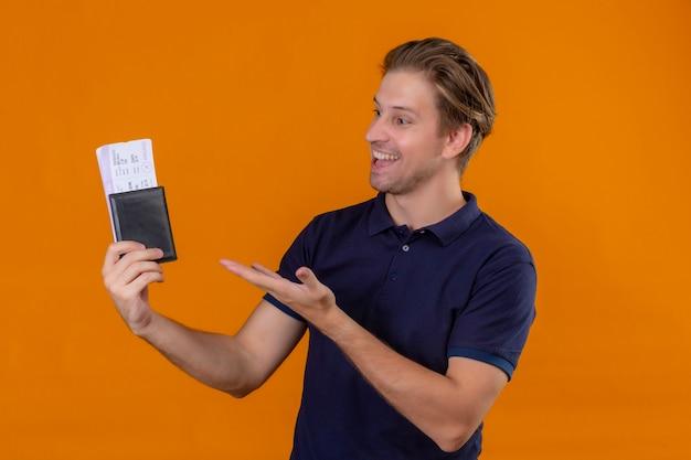 Uomo giovane viaggiatore bello che tiene i biglietti aerei che presentano con il braccio della mano che li guarda con il sorriso sul viso su sfondo arancione
