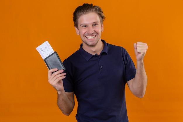 Молодой красивый путешественник мужчина держит авиабилеты, поднимает кулак после победы и счастливо улыбается, весело стоя на оранжевом фоне