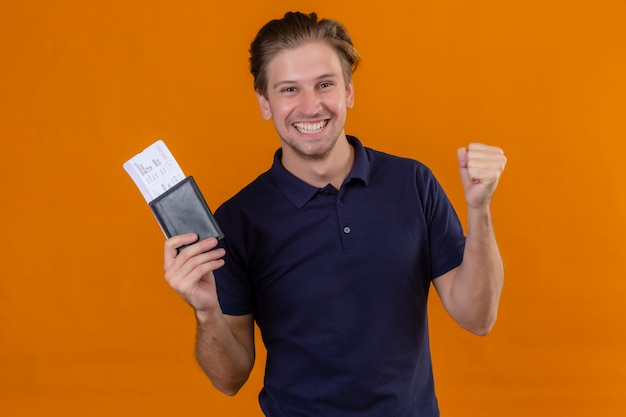 Young handsome traveler man holding air tickets raising fist after a victory exited and happy smiling cheerfully standing over orange background